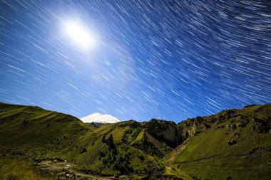 Moon over Mount Elbrus. Night landscape. Russia. Traces in the f