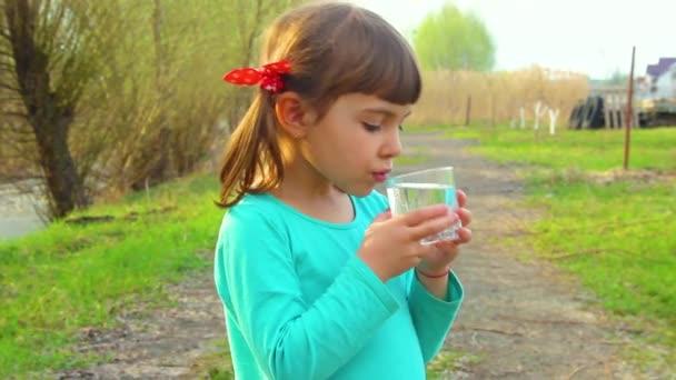 der Vater schenkt dem Kind ein Glas Wasser.