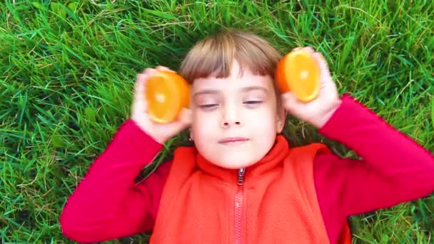 Dítě na zelené trávě s pomeranči.