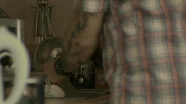 Tattoed man washes the dishes