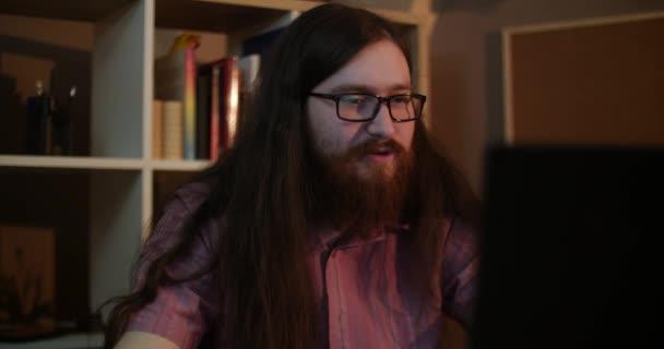 Egy fiatal szakállas férfi szemüveg nevet a számítógép