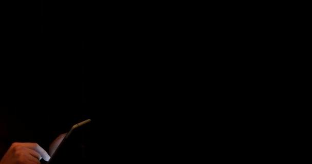 Un hombre guapo utiliza una tableta en un cuarto oscuro — Vídeo de ...
