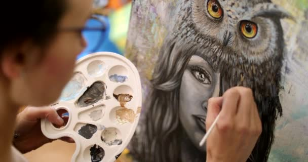 Girl artist paints a picture Shaman. Artist paints picture on canvas with acrylic paints in her workshop