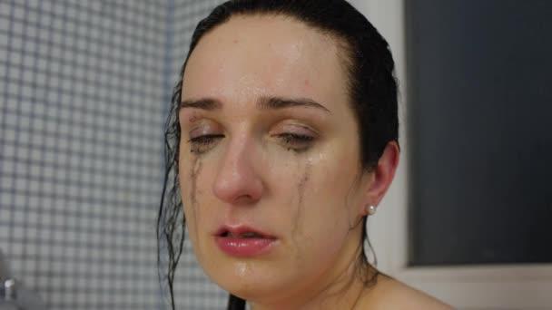 Érzéki nő csöpögő sminkkel sír a mosdóban. Portré. Közelkép.
