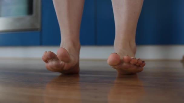 Žena tančí v obýváku. Detailní záběr na její nohy.