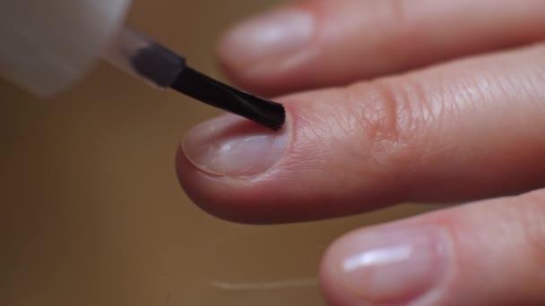 Frau lackiert ihre Fingernägel mit rosa Nagellack. 4k, Nahaufnahme, Zeitlupe