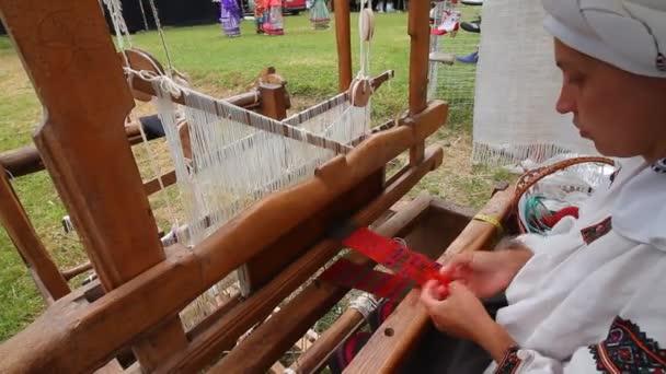 Yakushyntsi, Ukrajina - 22.06.2019: řemeslnice umělkyně pracuje na starověkém stavu, tkalcovský koberec na festivalu Live Fire Midsummer Pagan Ethno