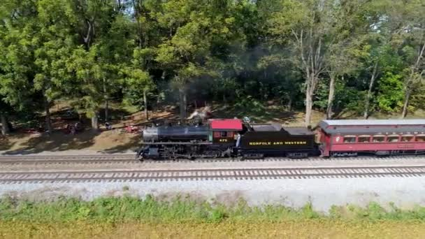 Strasburg, Pennsylvania, September 2019 - Aerial View of a Antique Steam Engine Puffing along Pulling Antique Passenger Cars Through Amish Farm Lands on a Sunny Autumn Day as Seen by a Drone
