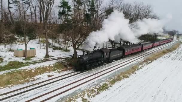 Strasburg, Pensylvánie, listopad 2018 - Ariel Pohled na parní motor a osobní automobily funící na farmě Amish po prvním sněhu sezóny