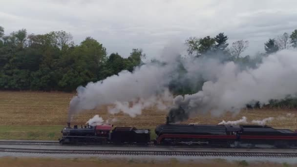 Aerial Side View of a Two Steam Locomotives Double Heading a Freight Train Puffing Along with Black Smoke and Steam
