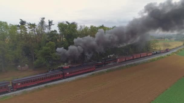 Strasburg, Pennsylvania, October 2019 - Aerial Angled View of a Two Steam Locomotives Double Heading a Freight Train Puffing Along Passing Passenger Cars with Black Smoke and Steam