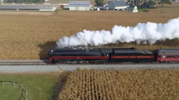 Strasburg, Pennsylvania, October 2019 - Aerial side by side view of a NW steam engine blowing steam and smoke while pulling passenger cars with view of farmlands on a sunny day