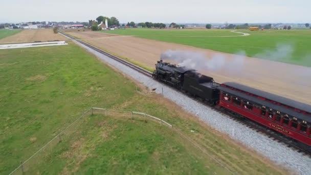 Letecký pohled na obnovený parní stroj blížící se k foukající páře a kouři při tahání starožitných osobních automobilů s výhledem na zemědělské pozemky za slunečného dne