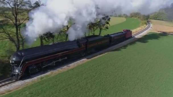 Strasburg. Pennsylvania, October 2019 - Aerial frontal close view of an antique restored steam locomotive traveling thru the countryside blowing black smoke and steam