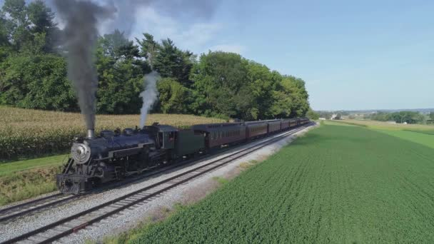 Aerial View of an Antique Restored Steam Engine Blowing Smoke with Passenger Cars pulling out of a Station on a Sunny Summer Day