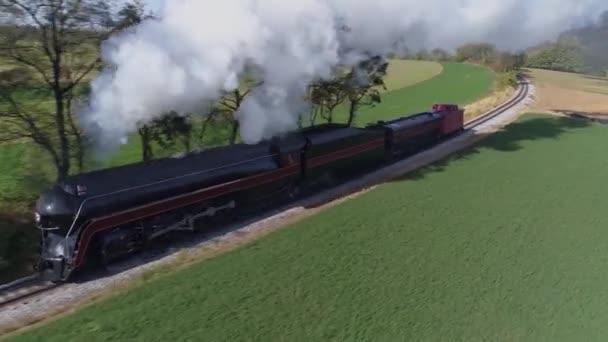 Letecký pohled na starožitnou obnovenou parní lokomotivu, která cestuje krajinou a fouká černý kouř a páru