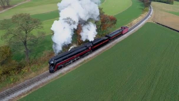 Vzduch nad hlavou pohled na starožitnou obnovenou parní lokomotivu, která cestuje podzimními stromy, jak fouká bílý kouř a páru