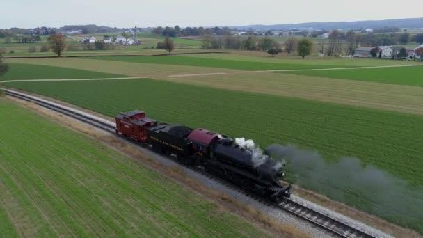 Strasburg, Pensylvánie, říjen 2019 - Letecký pohled na starožitnou obnovenou parní lokomotivu, která cestuje pozpátku krajinou, jak fouká černý a bílý kouř a páru