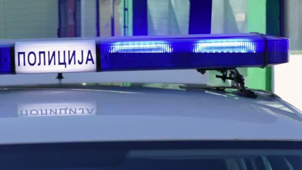 Policie modré blikající světla na autě; Blikající modré světlo na policejní auto na místě dopravní nehody. Cyrilice nápis