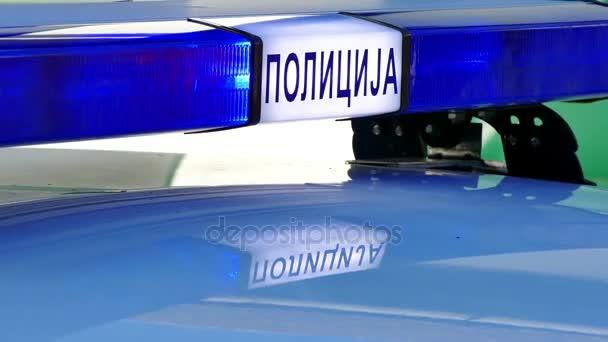 Blikající světlo na policejní auto; Blikající modré světlo na policejní auto na místě dopravní nehody. Cyrilice nápis