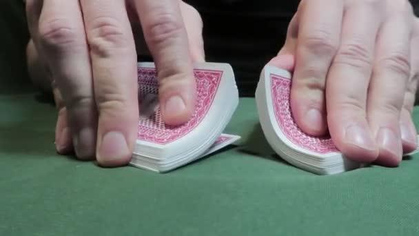 Riffle Shuffle. Mužská ruka šoupající karty na zeleném plátně. Detailní záběr. Hazard. Hazardní hry