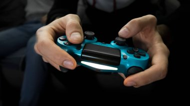 Male hands holding a gamepad playing game. One gamer person, close-up, front view