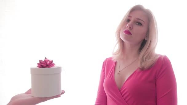 Trauriges Mädchen im roten Kleid mit rotem Lippenstift nimmt überrascht und erfreut ein Geschenk aus den Händen der Männer entgegen. Menschen und Geschenke. Eine festliche Stimmung. Romantik und Liebe. Valentinstag, internationaler Frauentag