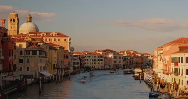 Včas Benátského kanálu s vodní dopravou. Pohybující se mraky nad městem. Italské městské budovy na řece. Cestovní destinace.