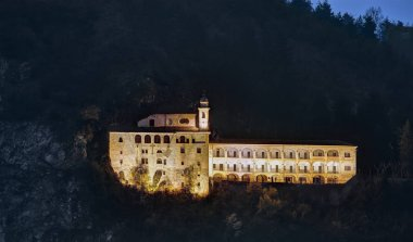 Sanctuary of Saint Lucia, clinging to the side of Mount Calvary, illuminated in the night . - The sanctuary of Santa Lucia, partially in a rocky cave, at Villanova Mondov, in Piedmont, Italy.