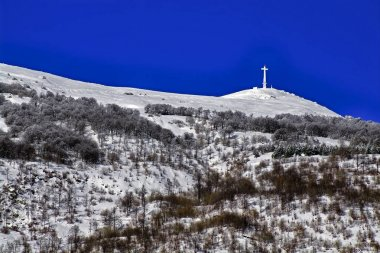 Bric Mindino and monumental cross under the snow. - View of the top of Mount Mindino, with its high (25 m + 2 of concrete base) cross in the snow. Maritime Alps, northern Italy.