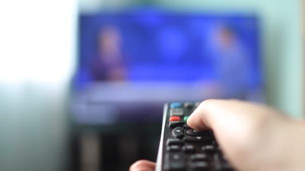 A lány otthon kapcsolók a távirányítóval csatornákat a TV-készülék, közelkép