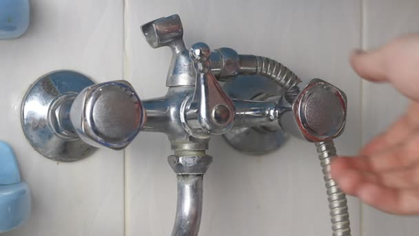ein Mann öffnet heißes Wasser, überprüft den Betrieb eines Wasserhahns, eine Nahaufnahme