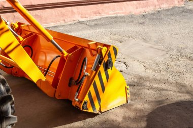 New multi-functional hydraulic bucket jaw mounted on a forklift in the city. Construction machinery, copy space