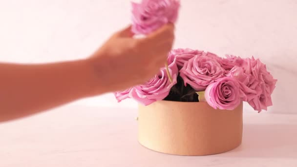 Female hands preparing a bouquet of pink roses