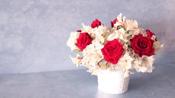 Female hands preparing a bouquet of red roses and alstroemeria