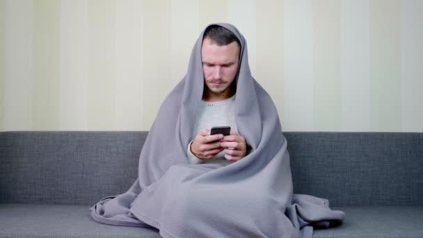 Kranker Mann mit Decke benutzt Smartphone Aufgebrachter junger Kerl sitzt auf der Couch bei hoher Temperatur. Akute Atemwegsinfektion. Erkältungsgrippe. Selbstmedikation zu Hause. 4k Filmmaterial
