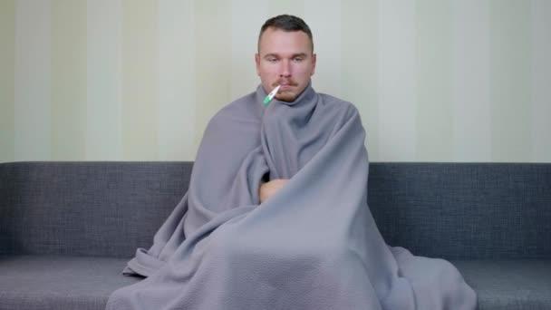 Kranker Mann mit Decke überzogen misst Temperatur mit Thermometer. Aufgebrachter junger Mann mit Fieber sitzt auf der Couch. Akute Atemwegsinfektion. Erkältungsgrippe. Selbstmedikation. 4k