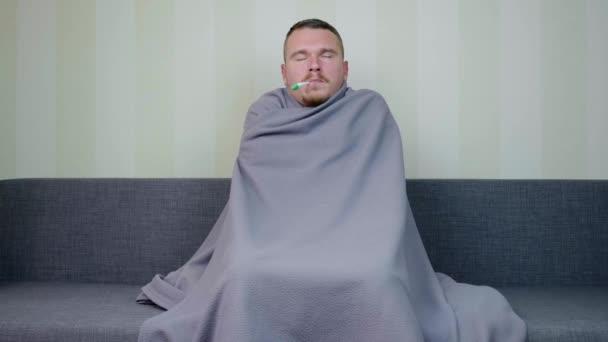 Kranker Mann mit Decke überzogen misst die Temperatur. Der aufgebrachte junge Mann zittert vor Fieber. Akute Atemwegsinfektion. Erkältungsgrippe. Selbstmedikation zu Hause. 4k Filmmaterial.