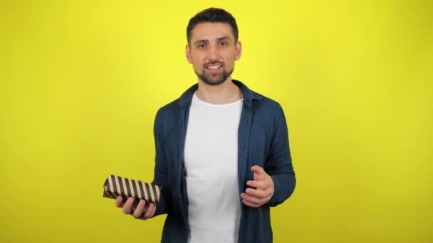 Mladý muž v bílém tričku hodí krabici s dárkem z ruky do ruky, podívá se do kamery a usměje se, žluté pozadí. Koncept svátků: Nový rok, Vánoce, Valentýnské narozeniny. 4kfootage