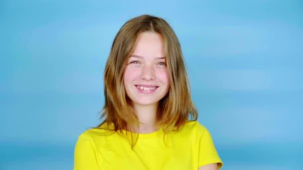 Šťastná dospívající dívka ve žlutém tričku se usmívá a rozhlíží se. Modré pozadí s kopírovacím prostorem. Emoce teenagerů. Záběry 4k