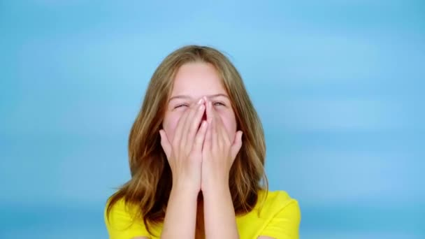 Happy teen girl in a yellow t-shirt is laughing, covers her face with her hands and looking at the camera. Blue background with copy space. Teenager emotions. 4k footage