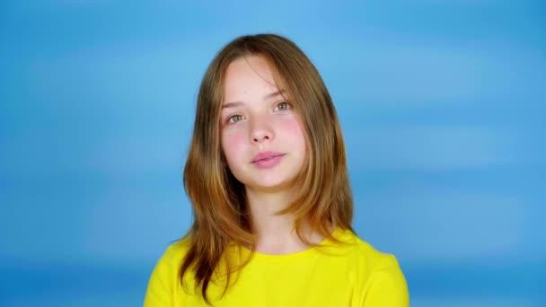 Teenie-Mädchen in gelbem T-Shirt blickt in die Kamera, nickt mit dem Kopf und sagt Ja. blauer Hintergrund mit Kopierraum. Teenager-Emotionen. 4k Filmmaterial