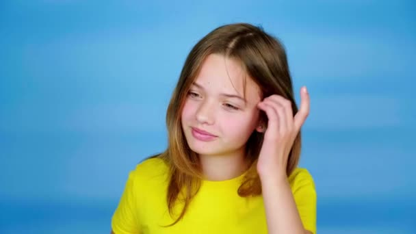 Teen girl in a yellow t-shirt is straightens her hair and throws them back. Blue background with copy space. Teenager emotions. 4k footage