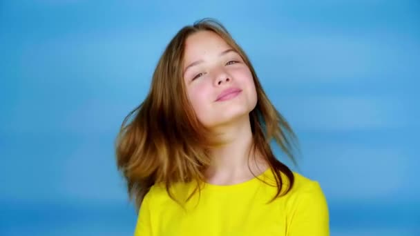 Happy teen girl in a yellow t-shirt is turns to the camera and smiles. Blue background with copy space. Teenager emotions. 4k footage