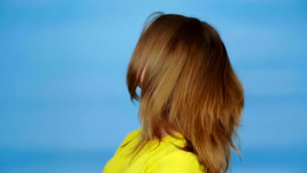 Teen girl in a yellow t-shirt is looking away and turns around her head. Blue background with copy space. Teenager emotions. 4k footage