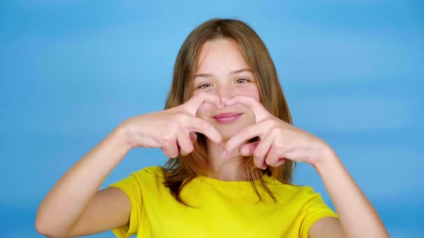 Teen girl in a yellow t-shirt showing heart shape, smiles and looking at camera. Blue background with copy space. Teenager emotions. 4k footage