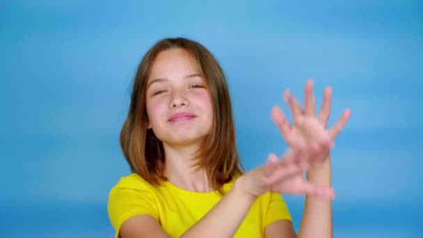 Happy teen girl in a yellow t-shirt is dancing, smiling and fools around. Blue background with copy space. Teenager emotions. 4k footage