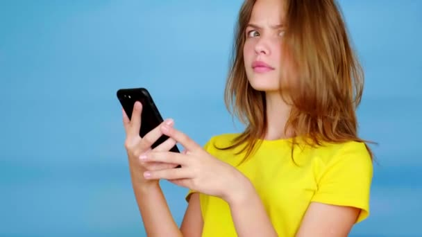 Teen girl in a yellow t-shirt is uses on smartphone, surprised, says wow and looks at camera. Blue background with copy space. Teenager emotions. 4k footage