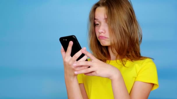 Teenie-Mädchen im gelben T-Shirt ist auf dem Smartphone unterwegs, überrascht, sagt wow und blickt in die Kamera. blauer Hintergrund mit Kopierraum. Teenager-Emotionen. 4k Filmmaterial