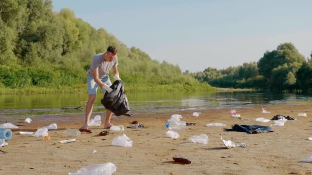 Man in a gray t-shirt and blue denim shorts is dancing and collects plastic trash on the banks of dry and polluted river, lake. Ecological catastrophy. Anthropogenic influence. 4K slowmotion footage.